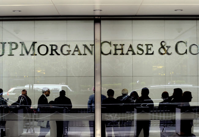 People stand inside of JPMorgan & Chase Co. headquarters in New York, U.S., on Wednesday, Oct. 10, 2012. JPMorgan & Chase Co. is scheduled to release earnings data on Oct. 12. Photographer: Peter Foley/Bloomberg